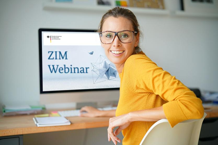 Frau sitzt vor ihrem Rechner und nimmt an einem Webinar teil